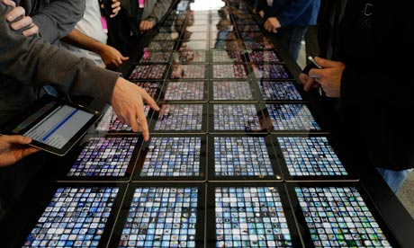 Mobile: Developers look over new apps being displayed on iPads at the Apple WWDC
